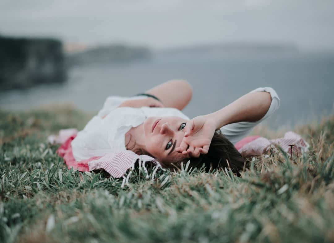 A young girl lying in the grass