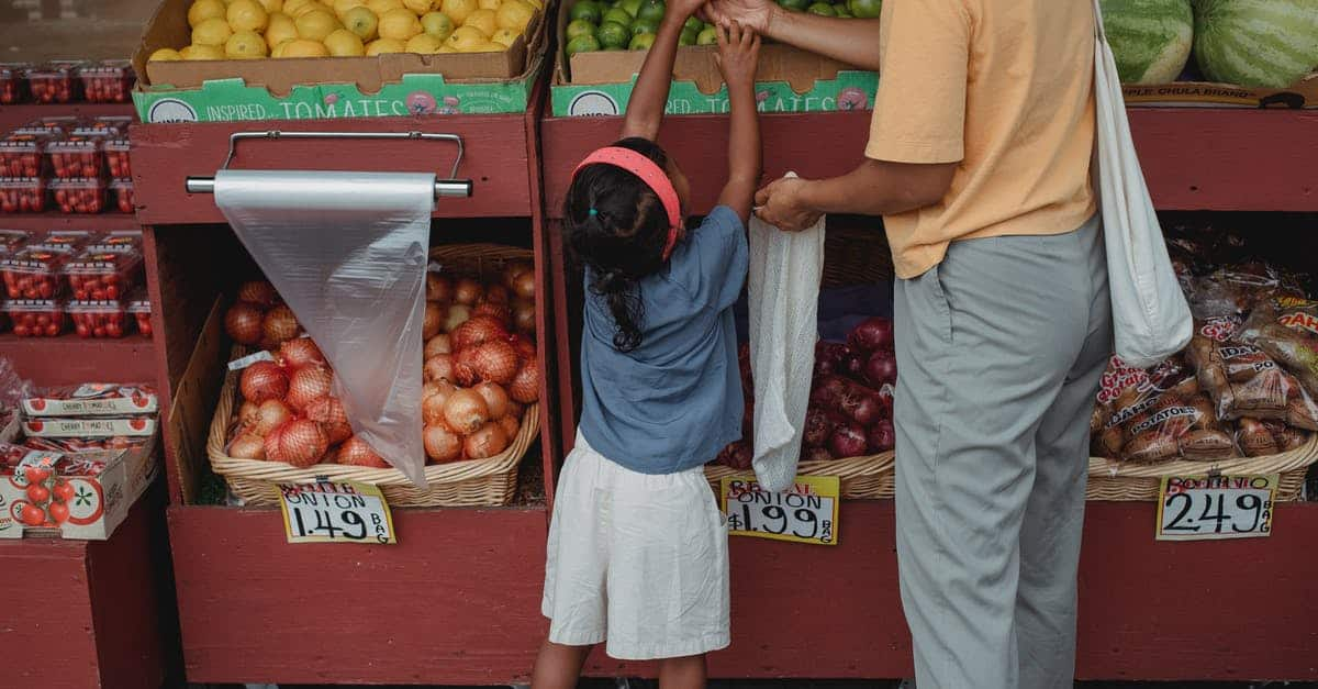 A person standing in front of a fruit stand